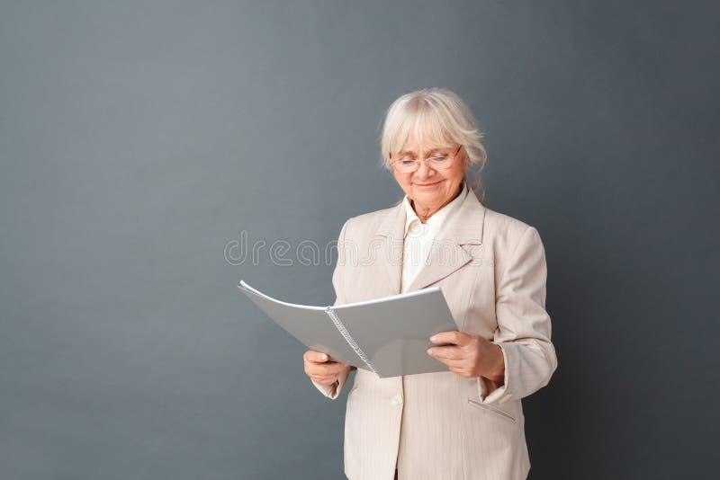 Hogere vrouw in fromal kostuum en glazenstudio die bij het grijze lezingsdagboek blij glimlachen wordt zich geïsoleerd bevinden d royalty-vrije stock fotografie