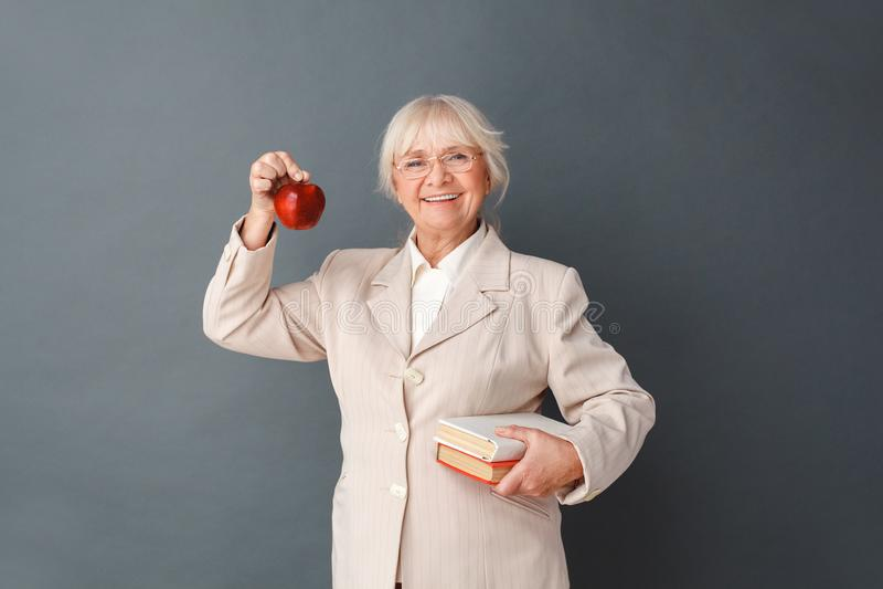 Hogere vrouw in fromal kostuum en glazenstudio die zich op grijs met boeken bevinden die appel houden kijkend gelukkige camera stock foto