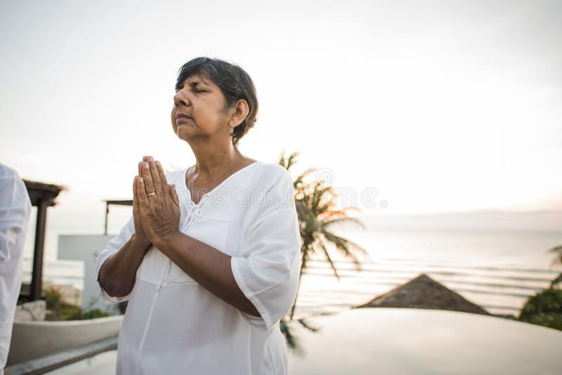 Hogere vrouw het praktizeren yoga in de ochtend royalty-vrije stock afbeeldingen