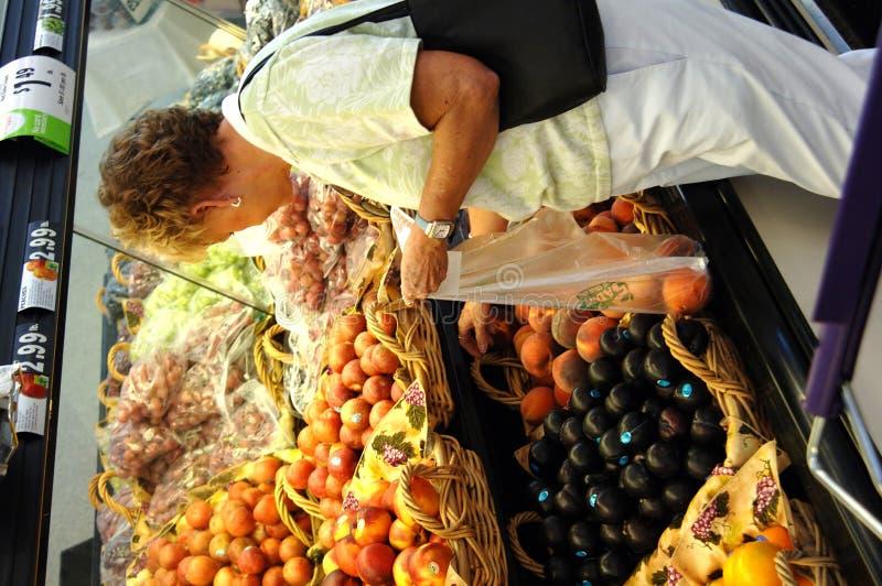 Hogere vrouw in kruidenierswinkelopslag royalty-vrije stock afbeeldingen