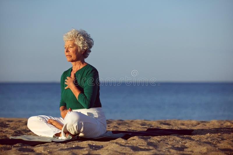 Hogere vrouw in meditatie door oceaan royalty-vrije stock foto's