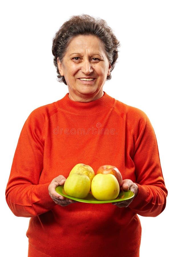 Hogere vrouw met appelen stock fotografie