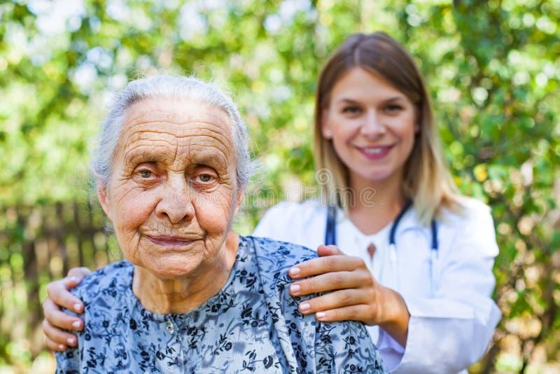 Hogere vrouw met arts in het park stock foto's
