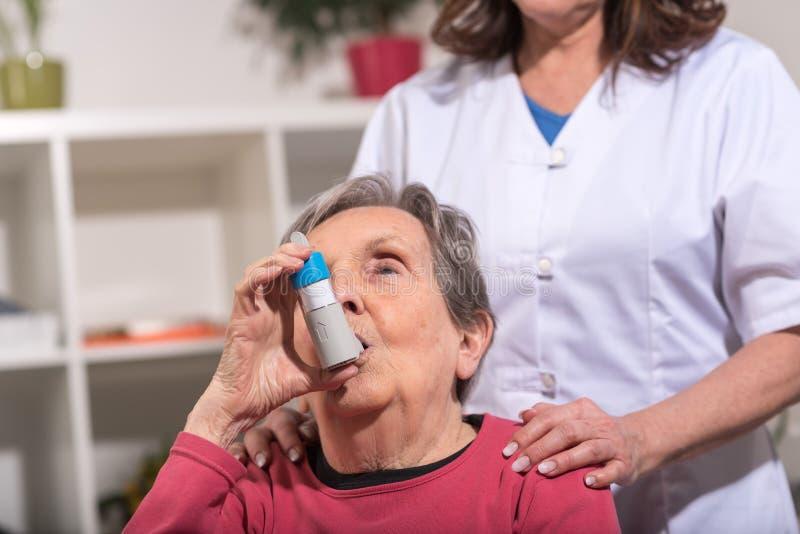 Hogere vrouw met astmainhaleertoestel stock foto's