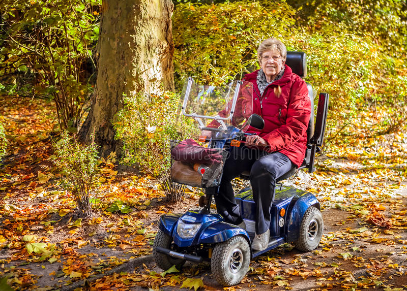 Hogere vrouw met autoped in het park stock afbeelding