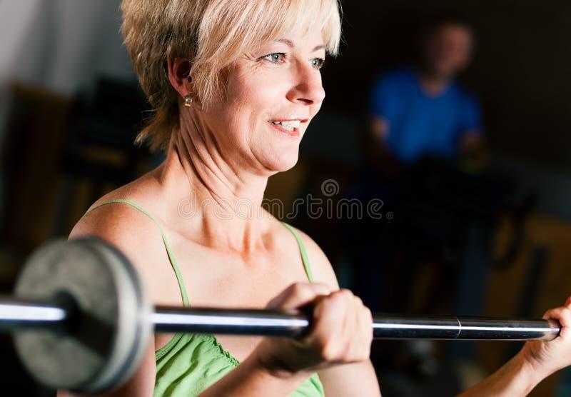 Hogere Vrouw met barbell in gymnastiek stock foto's