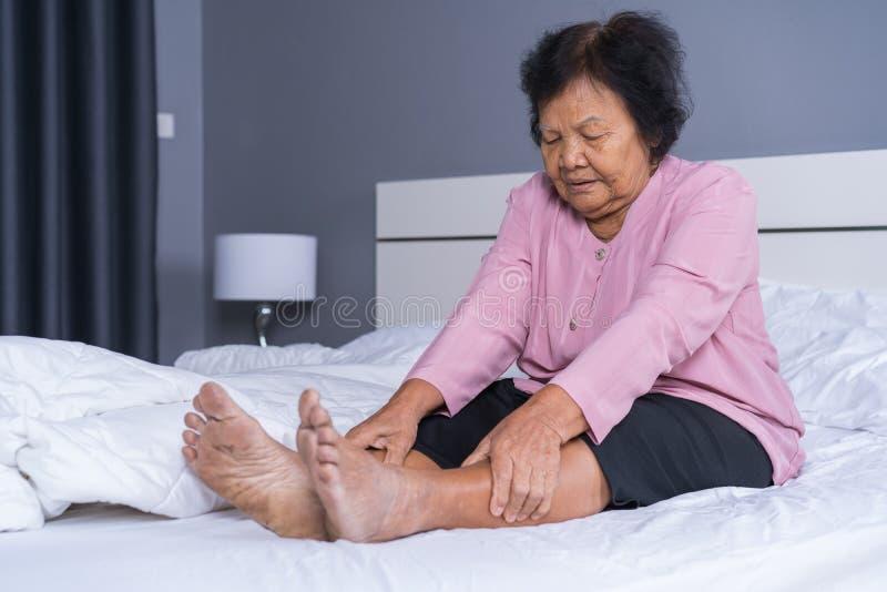 Hogere vrouw met beenpijn in bed royalty-vrije stock afbeelding