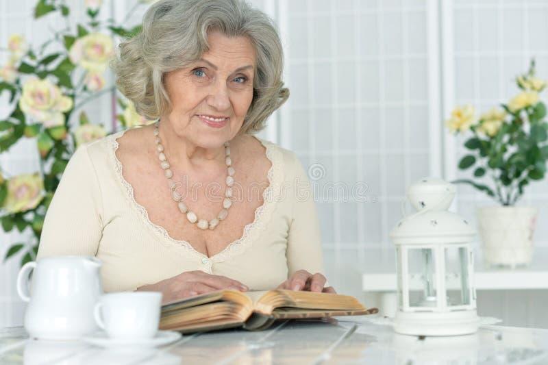 Hogere vrouw met boek stock afbeeldingen