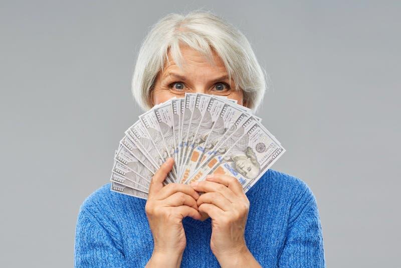 Hogere vrouw met de bankbiljetten van het honderd dollarsgeld stock afbeeldingen