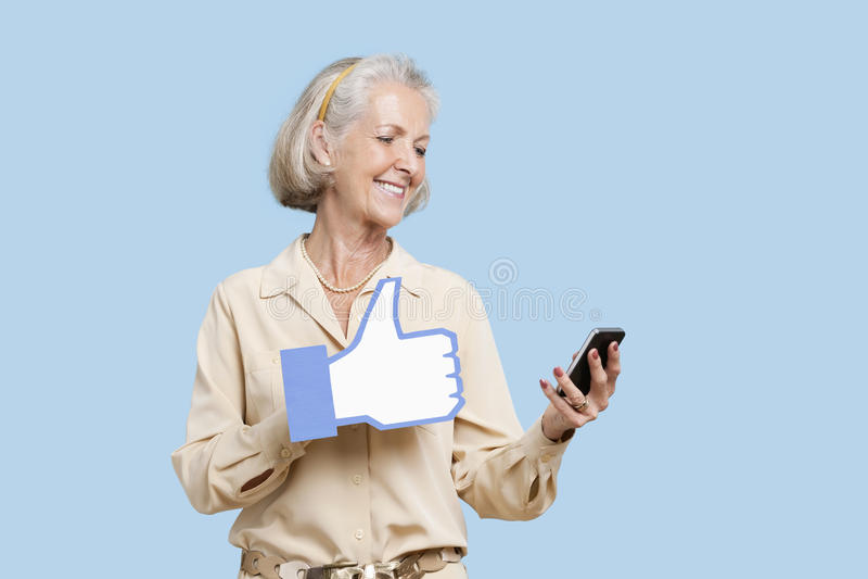 Hogere vrouw met de holdingsvervalsing van de celtelefoon zoals knoop tegen blauwe achtergrond stock fotografie