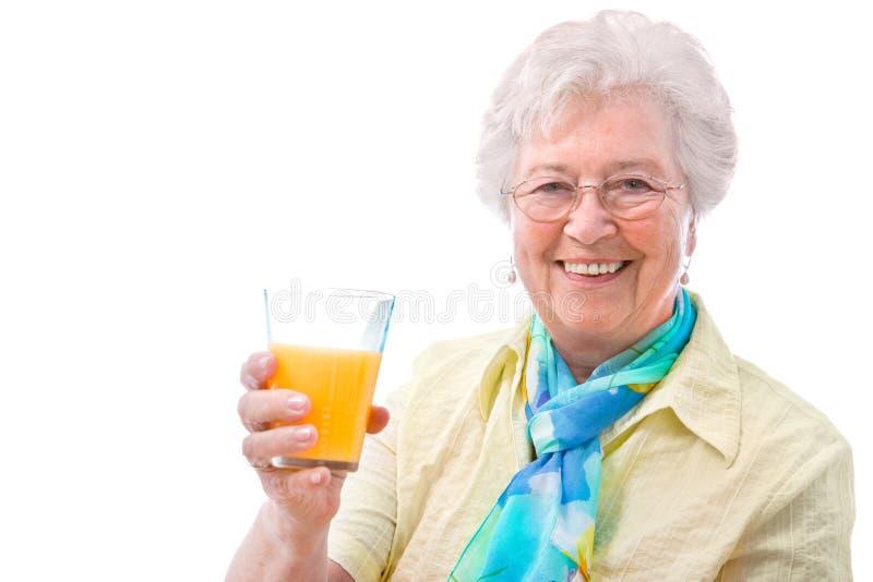 Hogere vrouw met een glas sap stock foto's