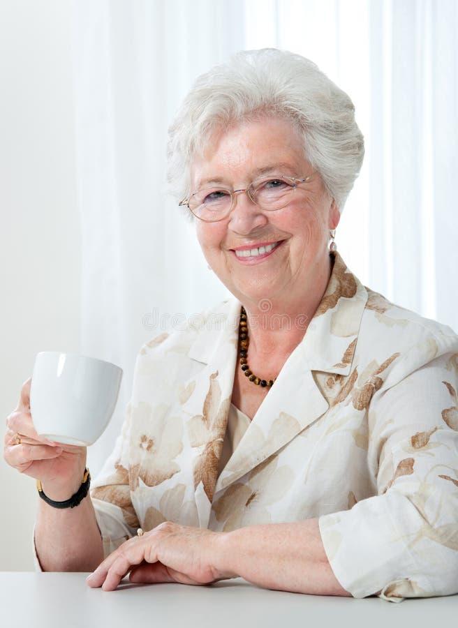 Hogere vrouw met een kop van koffie stock foto's