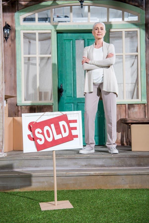Hogere vrouw met gekruiste wapens zich op portiek van nieuw huis bevinden en verkocht teken die op groen gras royalty-vrije stock foto's