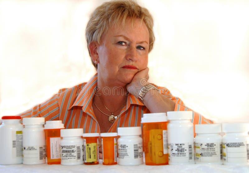 Hogere vrouw met geneeskundeflessen stock afbeeldingen