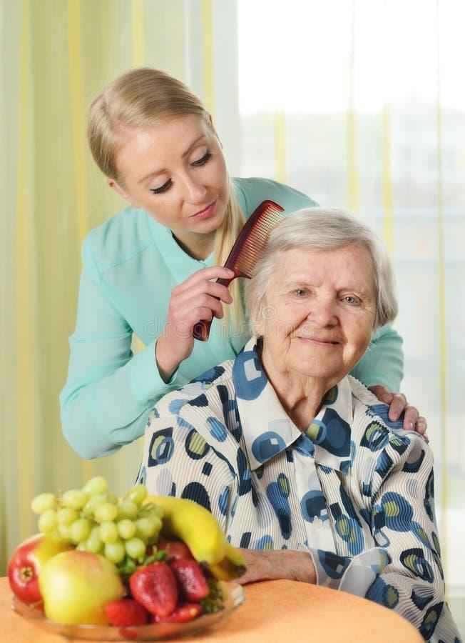 Hogere vrouw met haar caregiver stock foto