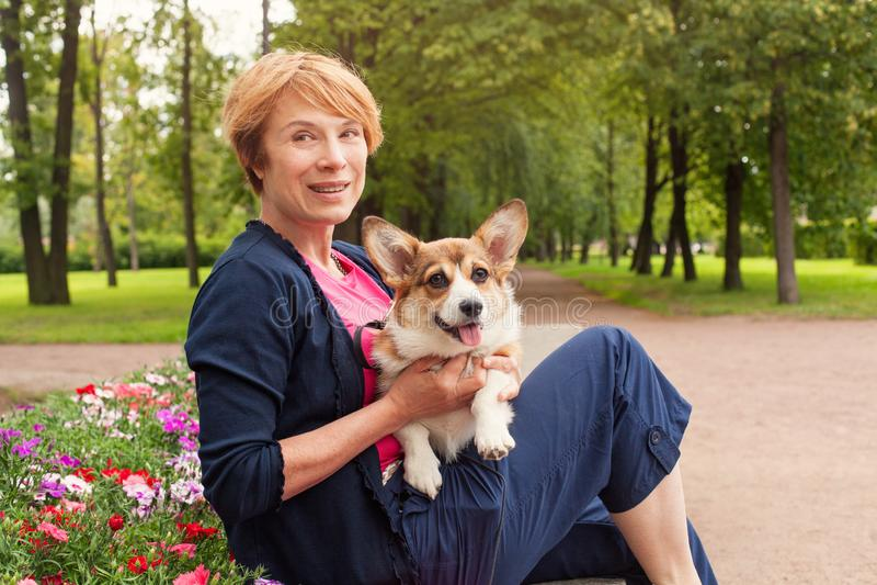 Hogere vrouw met haar leuke witte hond openlucht in de zomerpark royalty-vrije stock afbeeldingen