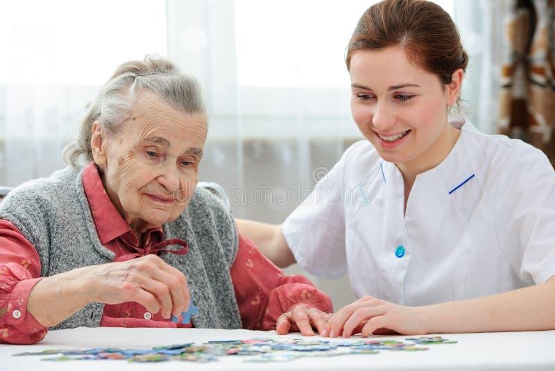 Hogere vrouw met haar oudere zorgverpleegster stock afbeelding