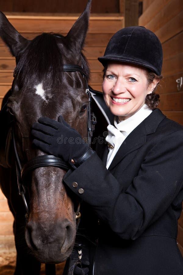Hogere vrouw met haar paard royalty-vrije stock foto's