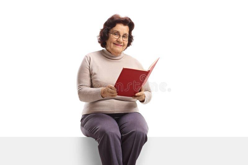 Hogere vrouw met het houden van een open boek en het zitten op een ruit royalty-vrije stock afbeelding