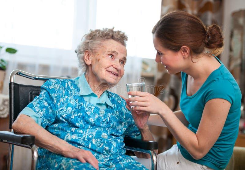 Hogere vrouw met huisverzorger stock foto's
