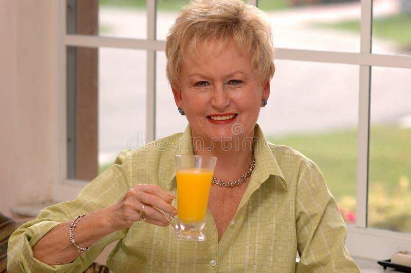 Hogere vrouw met jus d'orange royalty-vrije stock afbeeldingen