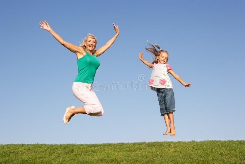 Hogere vrouw met kleindochter het springen in lucht stock foto's