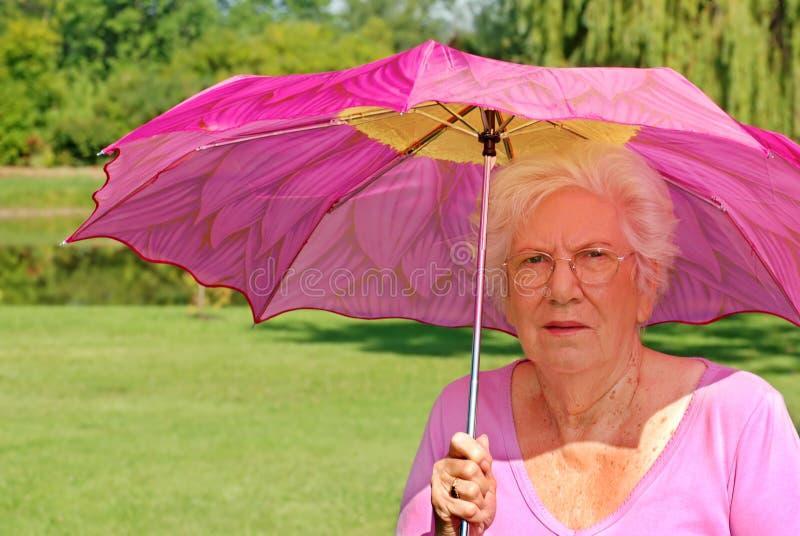 Hogere vrouw met kleurrijke paraplu royalty-vrije stock fotografie
