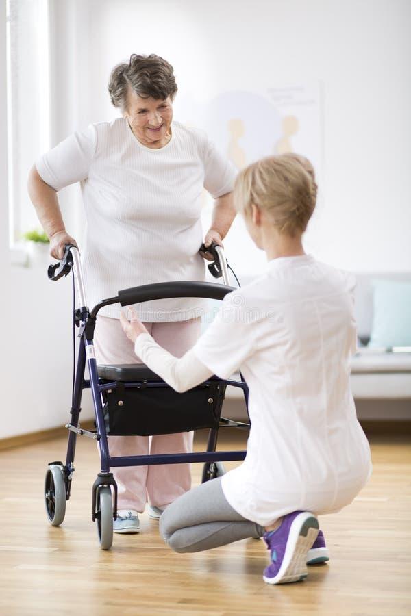 Hogere vrouw met leurder opnieuw proberen te lopen en nuttige fysiotherapeut die ondersteunend haar royalty-vrije stock foto's