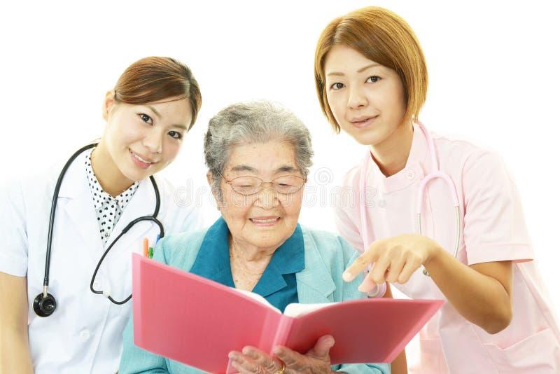 Hogere vrouw met medisch personeel stock afbeeldingen