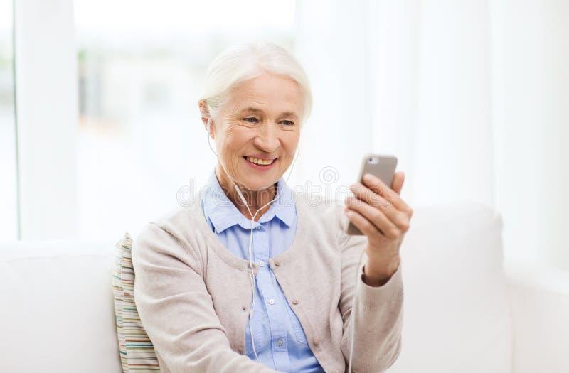 Hogere vrouw met smartphone en oortelefoons thuis stock afbeelding