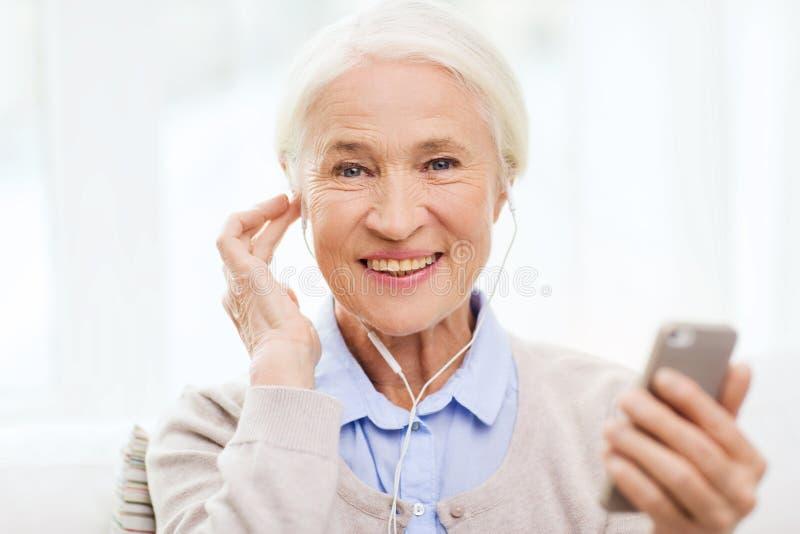 Hogere vrouw met smartphone en oortelefoons thuis stock foto's