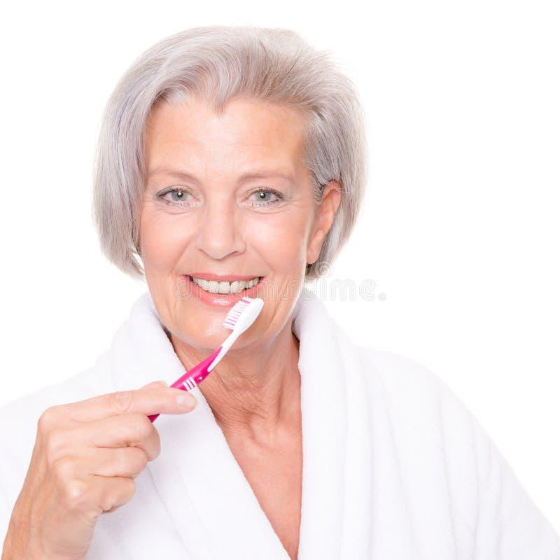 Hogere vrouw met tandenborstel stock foto's
