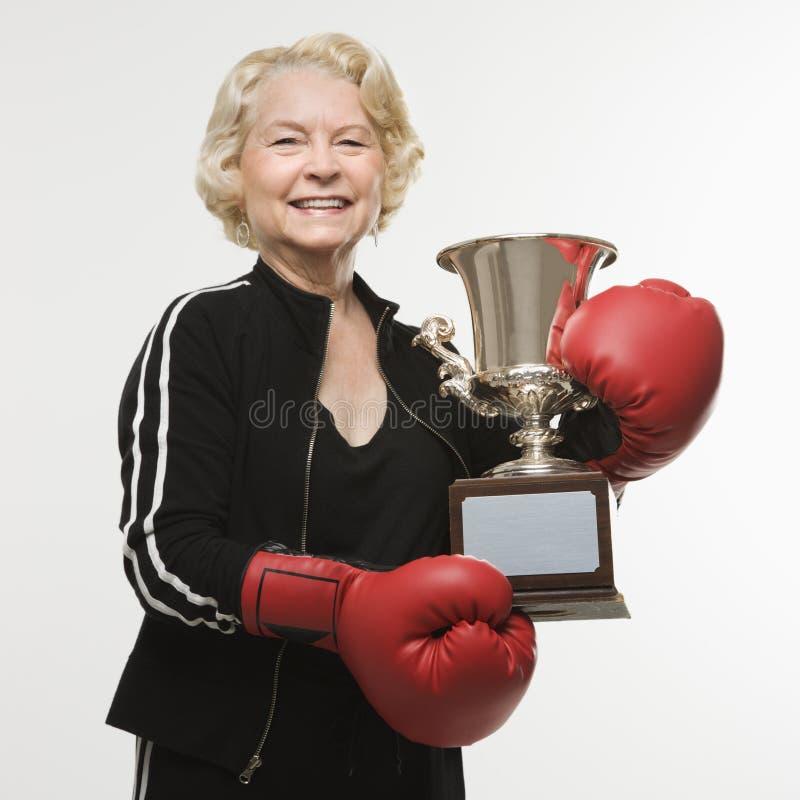 Hogere vrouw met trofee stock afbeelding
