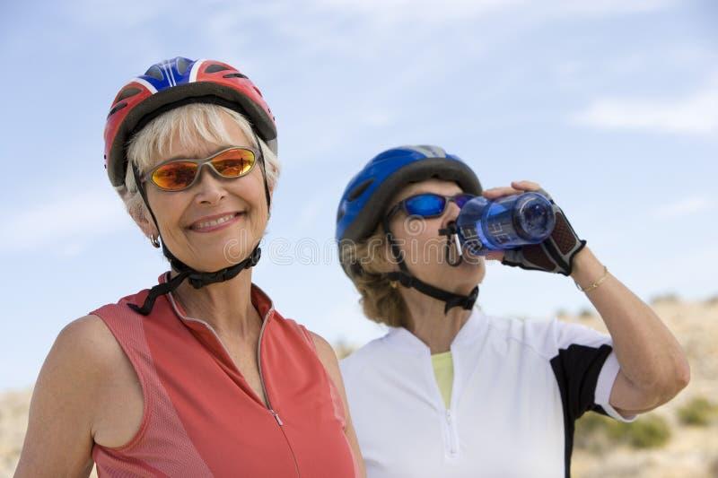 Hogere Vrouw met Vrienden Drinkwater op de Achtergrond royalty-vrije stock foto's