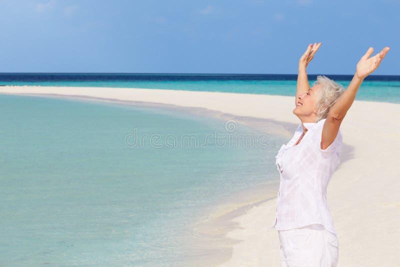 Hogere Vrouw met Wapens Uitgestrekt op Mooi Strand stock afbeelding