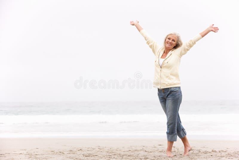 Hogere Vrouw met Wapens Uitgestrekt op Strand stock fotografie