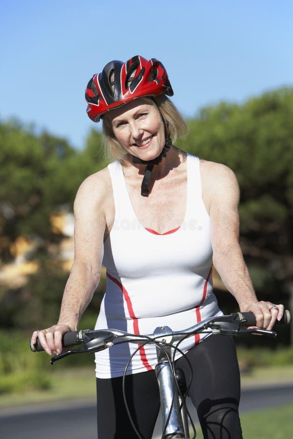 Hogere vrouw op cyclusrit stock fotografie