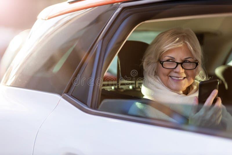 Hogere vrouw op de achterbank van een auto royalty-vrije stock foto