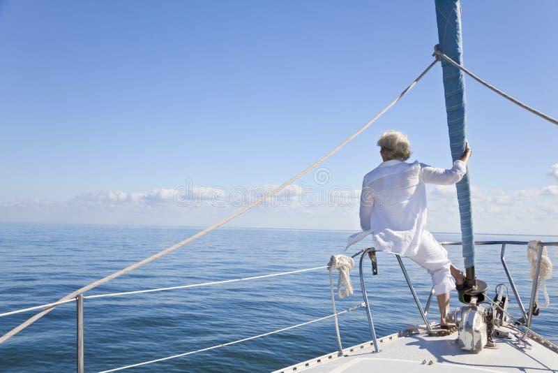 Hogere Vrouw op de Boog van een Boot van het Zeil stock afbeelding