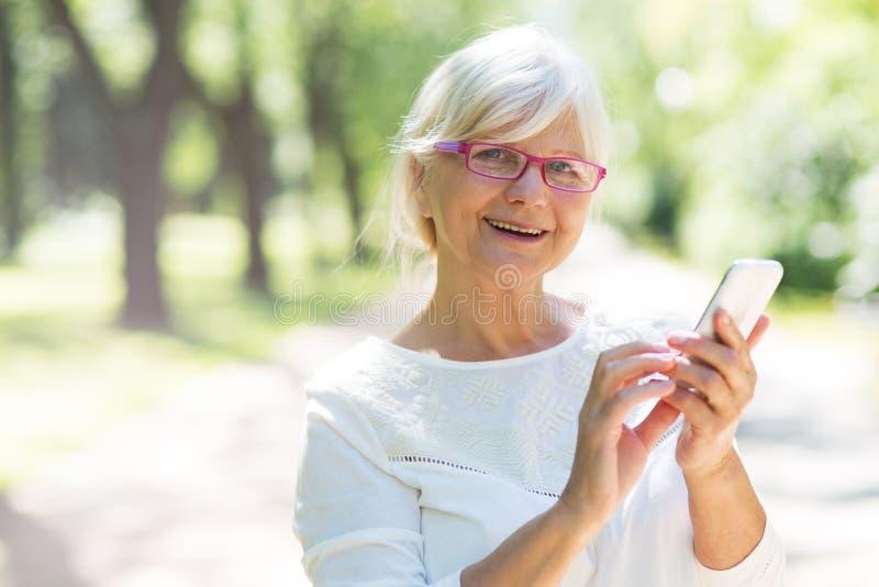 Hogere vrouw op de telefoon stock foto's