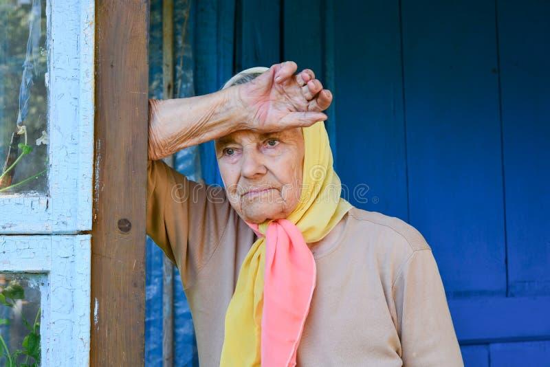 Hogere vrouw op de veranda van haar huis E Peinzende bejaarde stock foto's