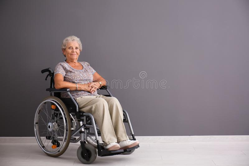 Hogere vrouw in rolstoel dichtbij grijze muur royalty-vrije stock afbeeldingen