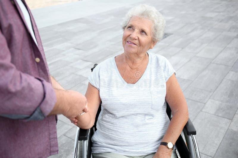 Hogere vrouw in rolstoel en haar echtgenoot in openlucht royalty-vrije stock afbeeldingen