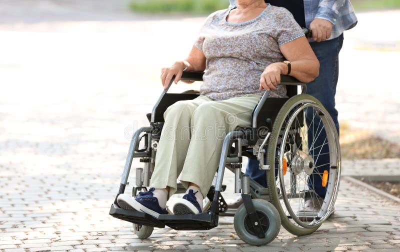 Hogere vrouw in rolstoel en haar echtgenoot in openlucht royalty-vrije stock foto's