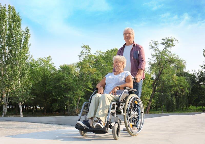 Hogere vrouw in rolstoel en haar echtgenoot in openlucht stock afbeeldingen
