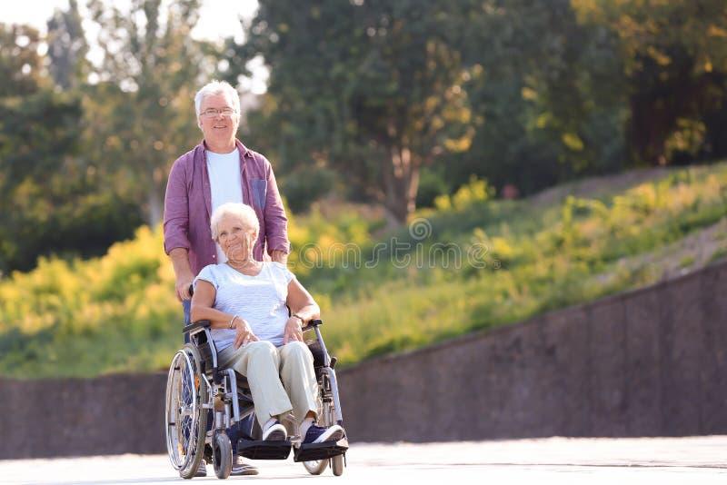 Hogere vrouw in rolstoel en haar echtgenoot in openlucht stock foto's