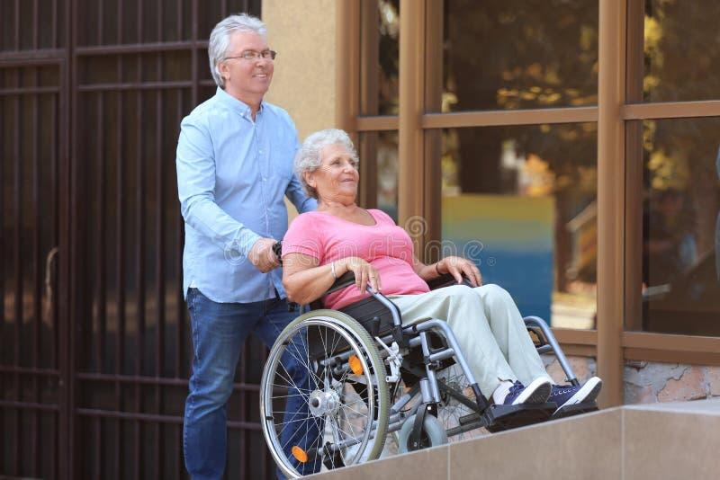 Hogere vrouw in rolstoel en haar echtgenootoprit in openlucht stock foto's