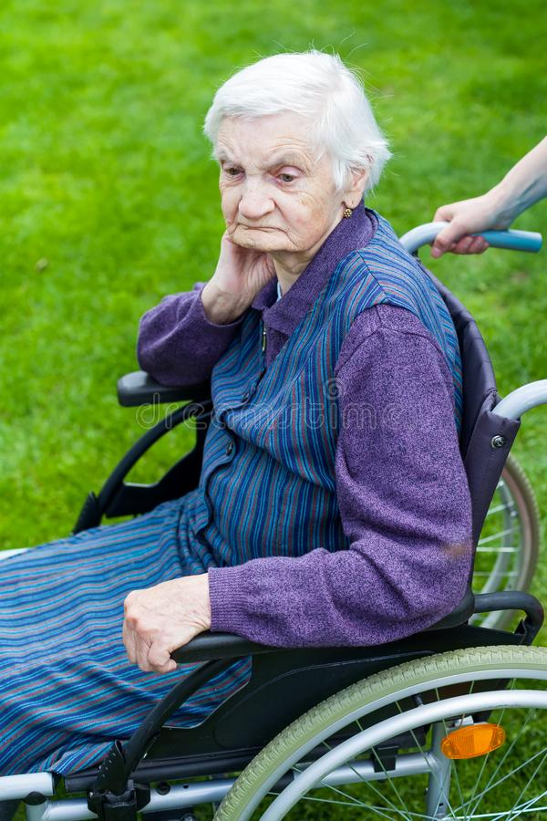 Hogere vrouw in rolstoel met verpleegster stock afbeelding