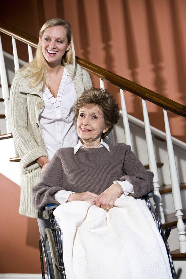 Hogere vrouw in rolstoel met verpleegster het helpen stock foto