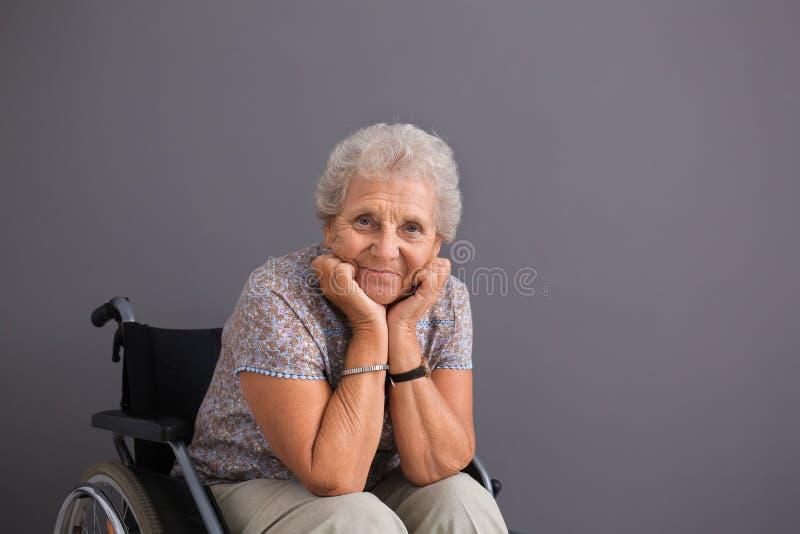 Hogere vrouw in rolstoel op grijze achtergrond royalty-vrije stock afbeelding
